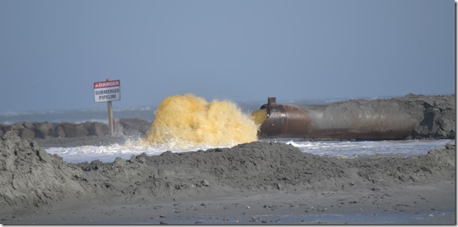 The U.S. Army Corps of Engineers — Charleston District digs up sand from the ocean floor and a pipe shoots the sand onto Folly Beach. (Photo/Liz Segrist)