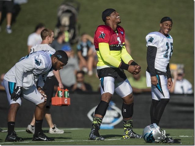 Carolina Panthers quarterback Cam Newton (red jersey) helps break the team down following a preseason scrimmage with the Miami Dolphins a Wofford College in August. (Photo by Melissa Melvin-Rodriguez)